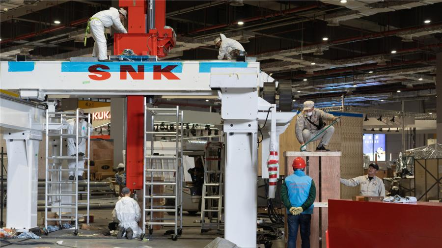 Workers install the platform for SNK, a Japanese video game hardware and software company, at the National Exhibition and Convention Center (Shanghai) on Oct. 28. (Photo/chinadaily.com.cn)