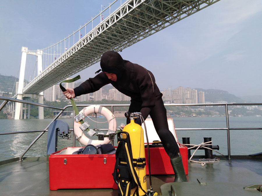 A diver from the armed police force stationed in Chongqing prepares to search the water on Sunday. (Photo by ZHOU YUKAI/FOR CHINA DAILY)