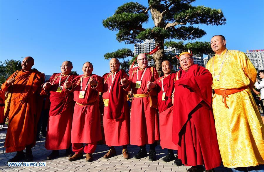 Guests for the fifth World Buddhist Forum pose for group photos during a tree planting activity in Putian, southeast China\'s Fujian Province, Oct. 28, 2018. A record number of over 1,000 Buddhists, scholars and representatives from 55 countries and regions attended the fifth World Buddhist Forum, which will last until Oct. 30.(Xinhua/Wei Peiquan)