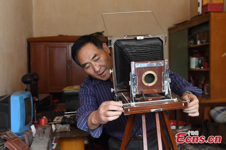 Photographer Wei Jixiong takes photos with an old-fashioned film camera at the Agan Photo Studio in Lanzhou City, Northwest China's Gansu Province, Oct. 27, 2018. Since Wei began working at the studio in the 1970s, he has continually used film cameras to take photos for customers despite the popularity of digital cameras. (Photo: China News Service/Yang Yanmin)