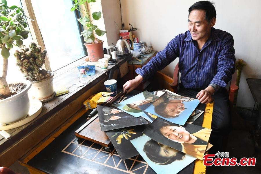 Photographer Wei Jixiong shows photos he has taken with old-fashioned film cameras at the Agan Photo Studio in Lanzhou City, Northwest China's Gansu Province, Oct. 27, 2018. Since Wei began working at the studio in the 1970s, he has continually used film cameras to take photos for customers despite the popularity of digital cameras. (Photo: China News Service/Yang Yanmin)