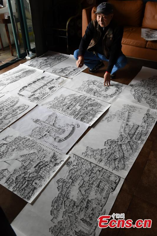 Qin Tingguang, in his seventies, shows his paintings drawn with ink brushes in his home in Southwest China's Chongqing Municipality, Oct. 29, 2018. Based on his memory, Qin has spent five years drawing 44 paintings of the city's landmarks 20 years ago. (Photo: China News Service/Zhou Yi)