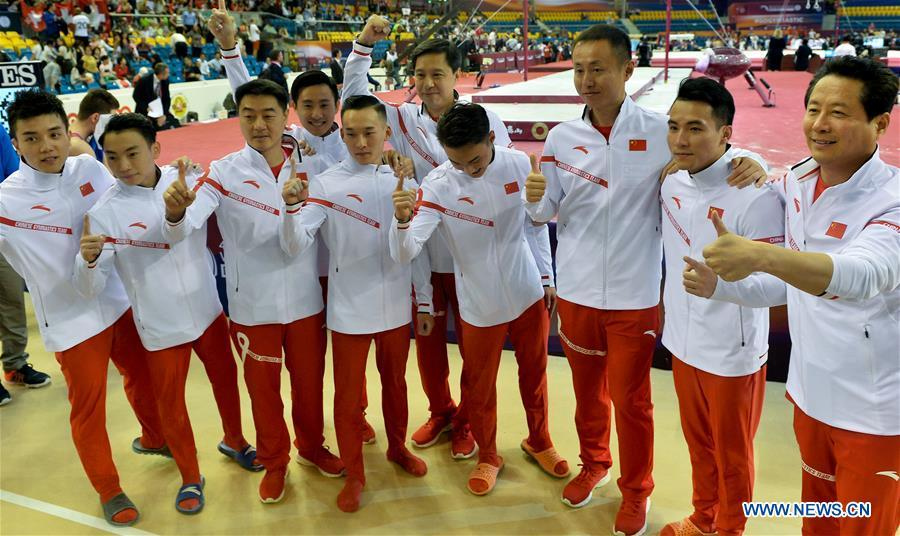 Members of team China celebrate after winning the Men\'s Team Final at the 2018 FIG Artistic Gymnastics Championships in Doha, capital of Qatar, Oct. 29, 2018. Team China won the gold medal. (Xinhua/Nikku)