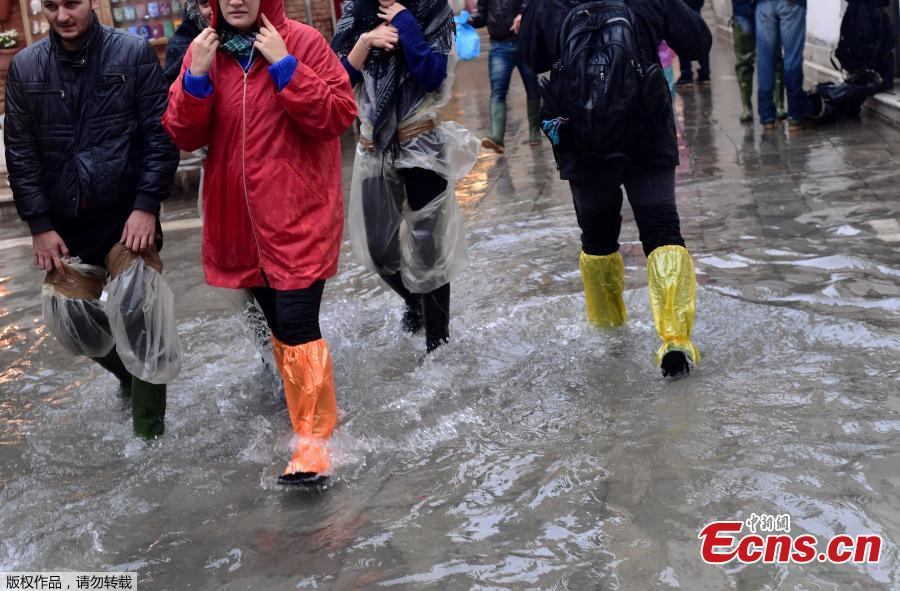 Tourists walk in the flooded streets during a high-water alert in Venice on October 29, 2018. The flooding, caused by a convergence of high tides and a strong Sirocco wind, reached 150 centimetres on October 29. (Photo/Agencies)