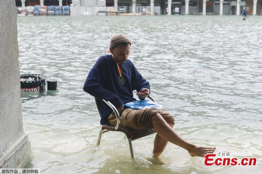A man sits on a chair in the flooded St. Mark Square during a high-water alert in Venice on October 29, 2018. The flooding, caused by a convergence of high tides and a strong Sirocco wind, reached around 150 centimetres on October 29, 2018. (Photo/Agencies)
