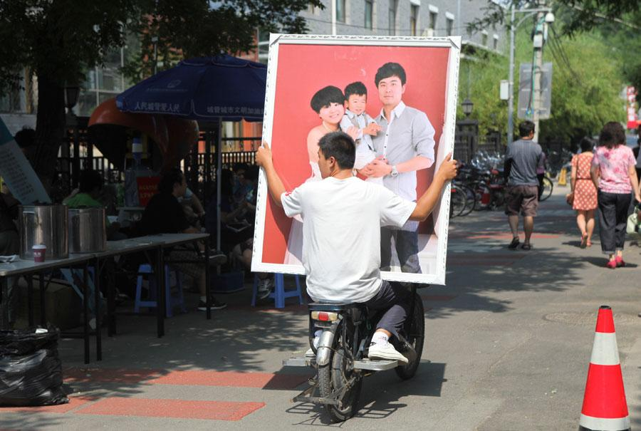 A man carries a photo of a happy family on the back of an electric bicycle in Neiwubu Street, Dongcheng district, Beijing, on June 8, 2012. (Photo by ZHANG JUSHENG/FOR CHINA DAILY)