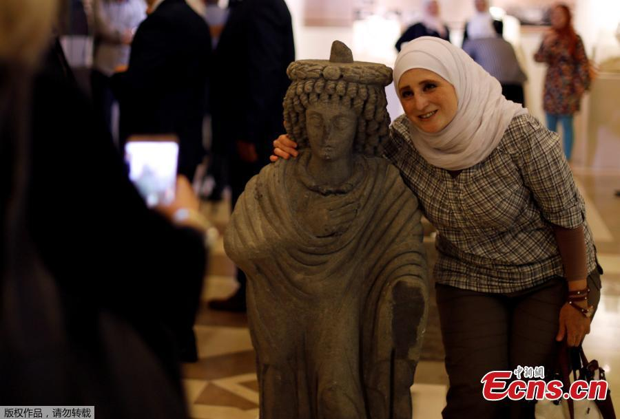 A woman poses for a picture with a restored sculpture, displayed in an exhibition, at the Opera house in Damascus, Syria October 3, 2018. Picture taken October 3, 2018. (Photo/Agencies)