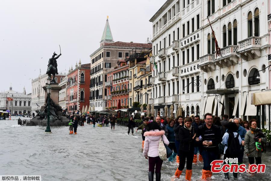 People walk in the flooded Riva degli Schiavoni during a high-water alert in Venice on October 29, 2018. The flooding, caused by a convergence of high tides and a strong Sirocco wind, reached around 150 centimetres on October 29, 2018. (Photo/Agencies)