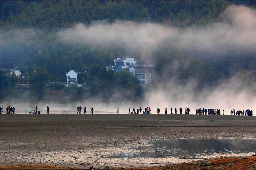 Morning mist casts a beautiful shadow above the Qishu Lake in Huangshan, East China\'s Anhui Province, Oct. 29, 2018. Located 2 kilometers from Hongcun village, a UNESCO World Cultural Heritage site, the lake offers a day tour of both natural scenery and historical gems. (Photo/Aisanewsphoto)