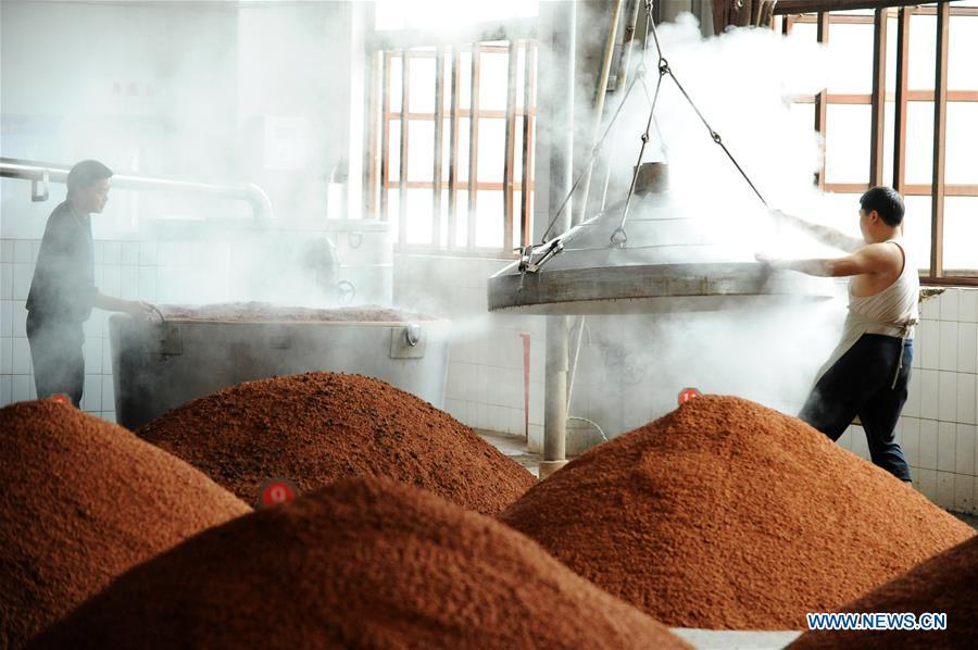 Workers process sorghum grains at a distillery in Maotai town in the city of Renhuai in southwest China\'s Guizhou Province, Oct. 23, 2018. Maotai is a small town in Renhuai City in mountainous Guizhou. What distinguishes it from other Chinese small towns is that it produces a famous brand of Chinese liquor Moutai, which often served on official occasions and at state banquets. The spirit, made from sorghum and wheat, takes up to five years for the whole production process, involving nine times of steaming, eight times of fermentation and seven times of distillation, before aged in clay pots. Moutai is also considered a luxury item that has long been a popular gift. China\'s alcohol industry earned about 1 trillion yuan in revenue in 2017. The total profits rose by 36 percent year on year to over 100 billion yuan, according to China National Light Industry Council. (Xinhua/Yang Wenbin)
