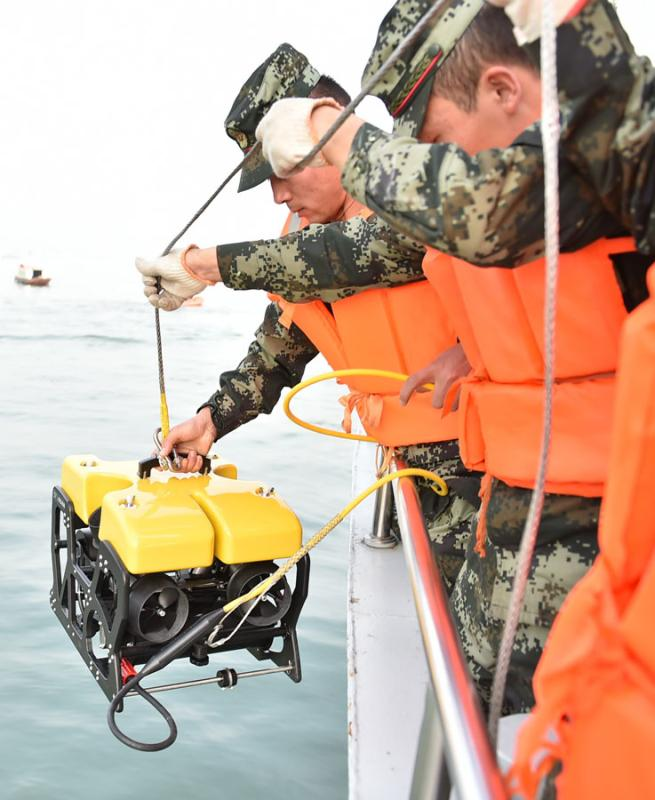 Armed police officers use an underwater robot to search for victims of the crash on Sunday. (Photo by Zhao Hui/For China Daily)