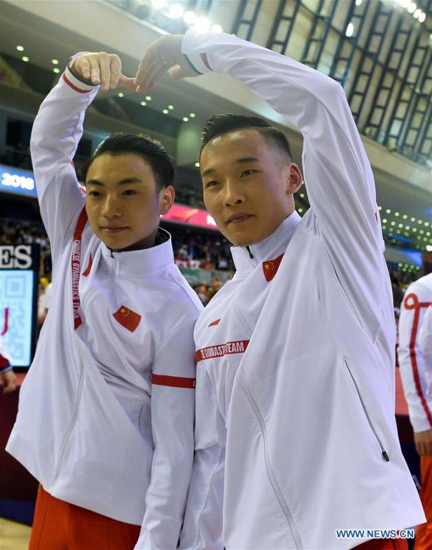 Xiao Ruoteng (R) and Zou Jingyuan of China celebrate after the Men\'s Team Final at the 2018 FIG Artistic Gymnastics Championships in Doha, capital of Qatar, Oct. 29, 2018. Team China won the gold medal. (Xinhua/Nikku)