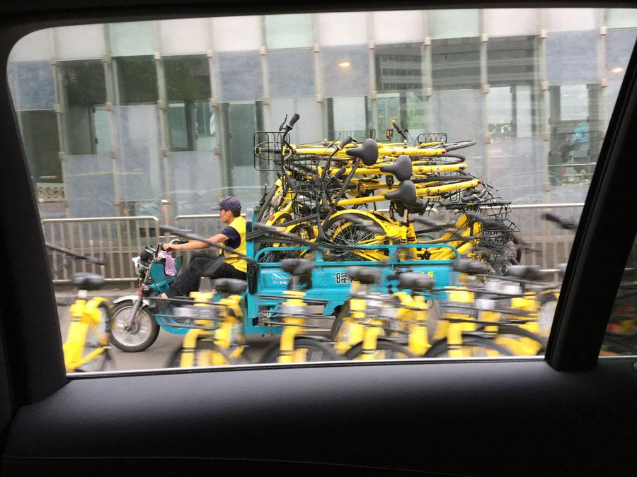 A warden transports shared bicycles in Chaoyang district, Beijing, on April 26, 2017.  (Photo/China Daily)