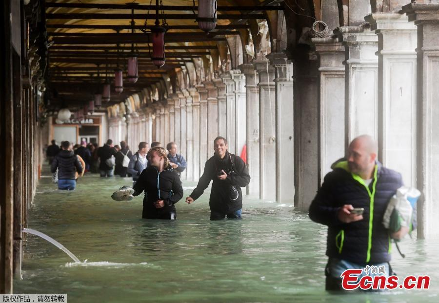 Tourists under arches next to the flooded St Mark\'s Square during a high-water alert in Venice on October 29, 2018. The flooding, caused by a convergence of high tides and a strong Sirocco wind, reached around 150 centimetres on October 29, 2018. (Photo/Agencies)