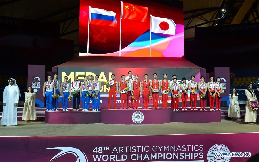 Team China (C), Team Russia (L) and Team Japan pose on the podium after the Men\'s Team Final at the 2018 FIG Artistic Gymnastics Championships in Doha, capital of Qatar, Oct. 29, 2018. Team China won the gold medal. (Xinhua/Nikku)