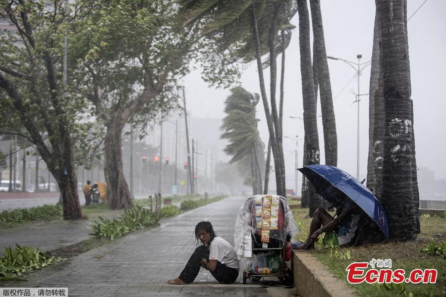 A streetside vendor shivers in the rain as weather patterns from Typhoon Yutu affect Manila Bay on Oct. 30, 2018. Typhoon Yutu slammed into the Philippines on Tuesday with fierce winds that sheared off roofs and snapped trees in half, after thousands were evacuated ahead of the powerful storm\'s arrival. (Photo/Agencies)