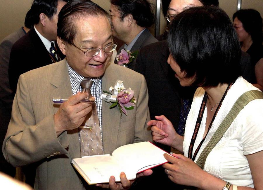 In this file photo, Jin Yong (L) signs a book for a reader during Hong Kong Book Fair in Hong Kong, south China, on July 22, 2001. Famous Chinese martial arts novelist Louis Cha Leung-yung, more widely known by his pen name Jin Yong, died at 94 at a hospital in Hong Kong on Tuesday. Cha created many widespread martial arts novels between 1955 and 1972. Cha, who also co-founded the Hong Kong daily newspaper Ming Pao, has been regarded as one of the greatest and most popular martial arts writers. (Xinhua/Shen Qiao)