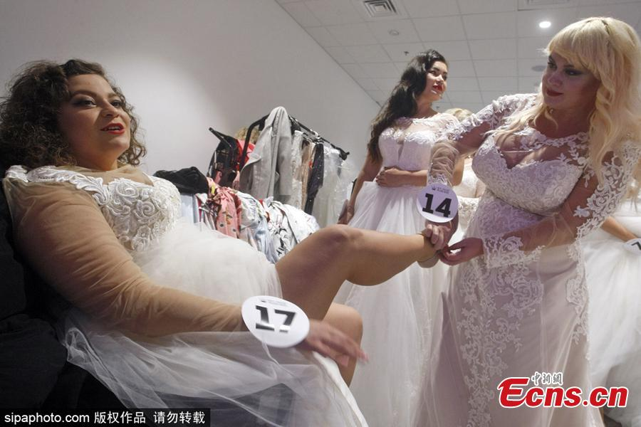Beauty queens help each other backstage before taking to the catwalk in a bid to be crowned the winner of Miss Ukraine Plus Size at the competition in Kiev, Oct. 29, 2018. The winner will represent the country at the Miss World Plus Size pageant in the Philippines next month. (Photo/Sipaphoto)