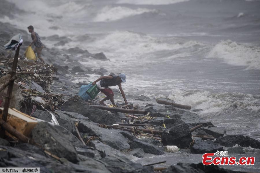 A scavenger collects recyclable materials along the breakwater amid strong waves as weather patterns from Typhoon Yutu affect Manila Bay on Oct. 30, 2018. Typhoon Yutu slammed into the Philippines on Tuesday with fierce winds that sheared off roofs and snapped trees in half, after thousands were evacuated ahead of the powerful storm\'s arrival. (Photo/Agencies)
