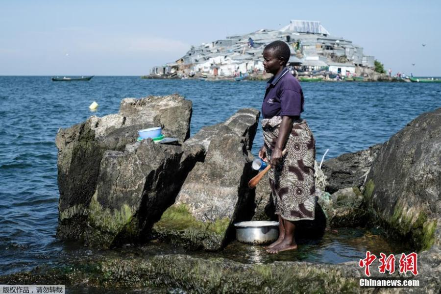 A woman cleans her items on Usingo island next to Migingo island on October 5, 2018 which is densely populated by residents fishing mainly for Nile perch in Lake Victoria on the border of Uganda and Kenya. A rounded rocky outcrop covered in metallic shacks, Migingo Island rises out of the waters of Lake Victoria like an iron-plated turtle. The densely-populated island is barely a quarter of a hectare large, its residents crammed into a hodge-podge of corrugated-iron homes, with seemingly little but a few bars, brothels and a tiny port to boast of. (Photo/Agencies)