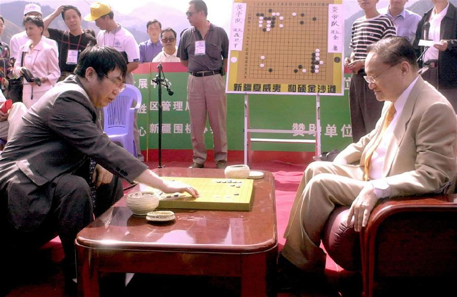 In this file photo, Jin Yong (R, front) plays against Chinese go chess master Nie Weiping, northwest China\'s Xinjiang Uygur Autonomous Region, on Aug. 5, 2001. Famous Chinese martial arts novelist Louis Cha Leung-yung, more widely known by his pen name Jin Yong, died at 94 at a hospital in Hong Kong on Tuesday. Cha created many widespread martial arts novels between 1955 and 1972. Cha, who also co-founded the Hong Kong daily newspaper Ming Pao, has been regarded as one of the greatest and most popular martial arts writers. (Xinhua/Luo Xiaoguang)