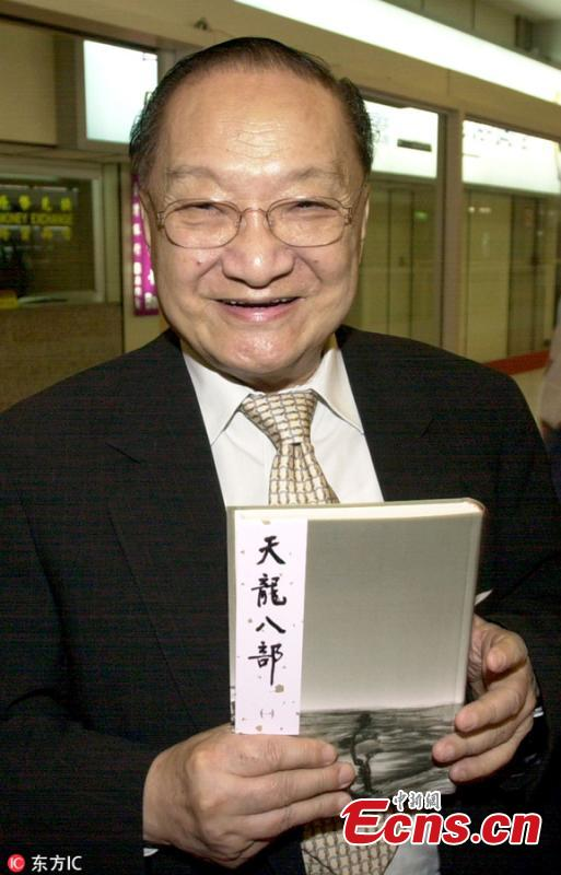 Chinese martial arts novelist Louis Cha holds one of his popular novels Demi-Gods and Semi-Devils upon his arrival at an airport in Taiwan, Sept. 19, 2005. (Photo/IC)