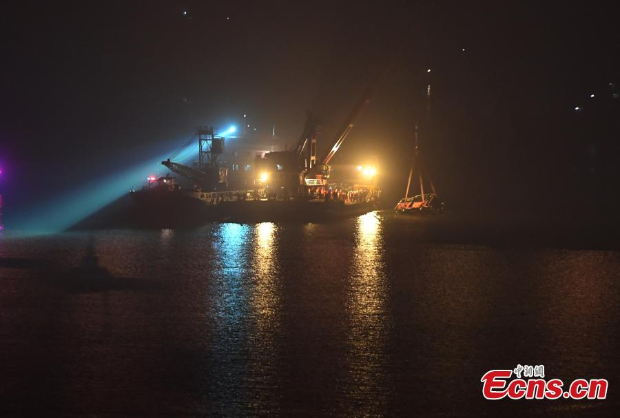 Rescuers on Wednesday night salvaged the wreck of a bus that plunged into the Yangtze River in Chongqing Municipality leaving at least nine people dead. The bus was pulled out of water by a floating crane at about 11:30 p.m.. Rescuers are expected to enter the bus to search for bodies of victims. The bus veered onto the wrong side of the road and collided into an oncoming car before breaking through road fencing and falling off a bridge in Chongqing\'s Wanzhou District on Sunday.(Photo: China News Service/ Chen Chao)