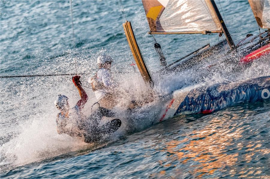 Sailors steer a two-man catamaran as water splashes during the 2018 Extreme Sailing Series Qingdao Mazarin Cup. (Photo by Zhong Weihua/for chinadaily.com.cn)  The 2018 Extreme Sailing Series Qingdao Mazarin Cup unveiled on Wednesday the award-winning photography of the event.  Selected through a contest, the photos captured moments from the 12-strong international Flying Phantom fleet during the sailing competition in Qingdao, Shandong Province, held from Sept. 30 to Oct. 3.  The Extreme Sailing Series, established in 2007, is the original Stadium Racing sailing circuit designed for spectators, delivering high-performance action close to the shore and putting guests at the heart of the battle.  The event has bolstered the coastal city of Qingdao\'s reputation as the home of Chinese sailing.