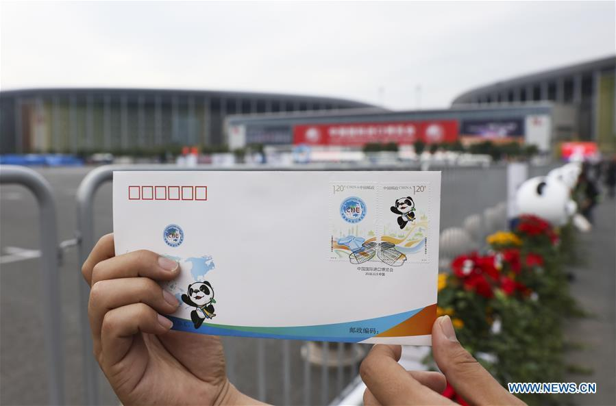 A journalist presents the first day cover with stamps released to commemorate the China International Import Expo (CIIE) at the National Exhibition and Convention Center in Shanghai, east China, Nov. 5, 2018.(Xinhua/Lan Hongguang)