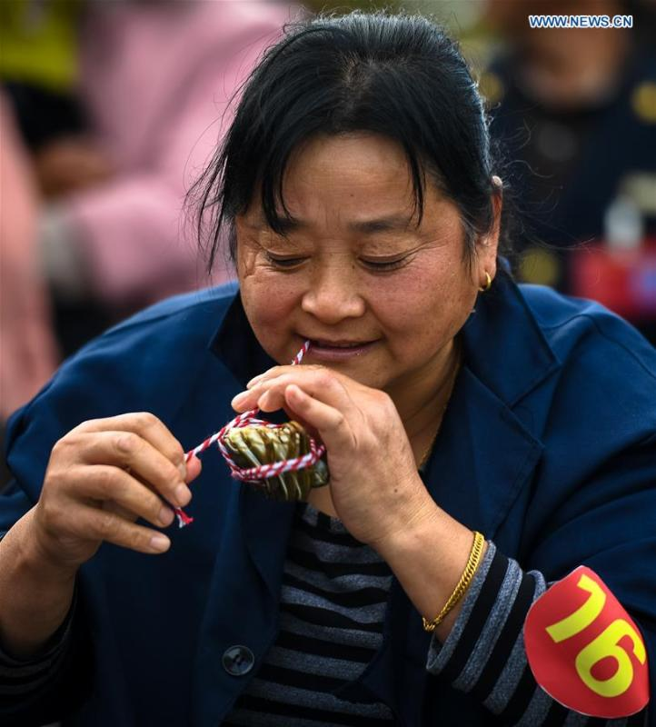 A woman takes part in a crab binding contest in Sihong County, east China\'s Jiangsu Province, Nov. 3, 2018. A total of 100 contestants participated in the event on Saturday. The winner bound 30 crabs within 3 minutes and 59 seconds. (Xinhua/Li Xiang)