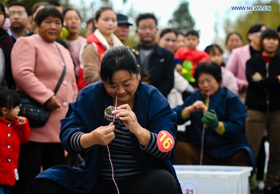 People take part in a crab binding contest in Sihong County, east China\'s Jiangsu Province, Nov. 3, 2018. A total of 100 contestants participated in the event on Saturday. The winner bound 30 crabs within 3 minutes and 59 seconds. (Xinhua/Li Xiang)