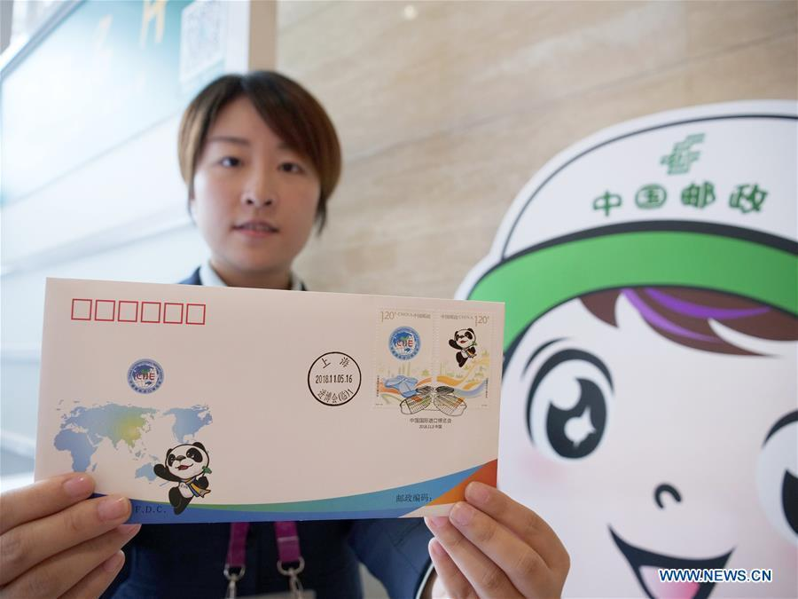 A staff member shows the first day cover with stamps released to commemorate the China International Import Expo (CIIE) at the National Exhibition and Convention Center in Shanghai, east China, Nov. 5, 2018.(Xinhua/Wang Yiliang)