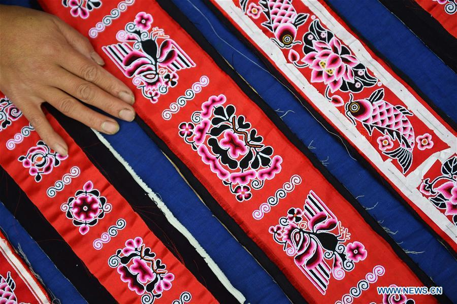 Yang Xinghe shows embroidered decorations for Miao costumes at Xinjiang Village in Taijiang County of Qiandongnan Miao and Dong Autonomous Prefecture, southwest China\'s Guizhou Province, on Nov. 4, 2018. Born with hearing loss, Yang Xinghe, 28, is a female of the Miao ethnic group, who are engaged in Miao embroidery at the village. She learned embroidery from her mother when she was only a child, and has been a locally well-known master now. (Xinhua/Liu Kaifu)