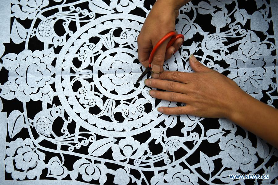Yang Xinghe designs embroidery patterns at Xinjiang Village in Taijiang County of Qiandongnan Miao and Dong Autonomous Prefecture, southwest China\'s Guizhou Province, on Nov. 4, 2018. Born with hearing loss, Yang Xinghe, 28, is a female of the Miao ethnic group, who are engaged in Miao embroidery at the village. She learned embroidery from her mother when she was only a child, and has been a locally well-known master now. (Xinhua/Liu Kaifu)