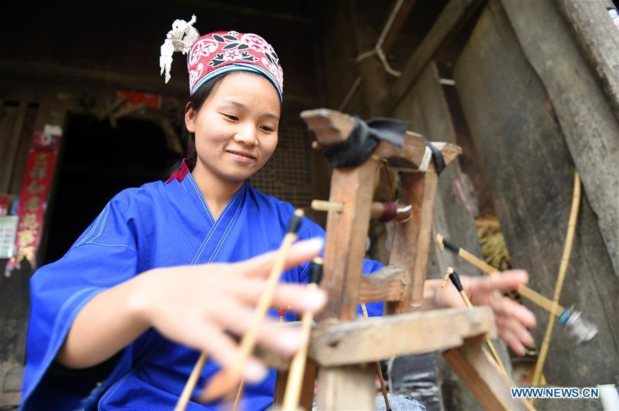 Yang Xinghe weaves ribbon at Xinjiang Village in Taijiang County of Qiandongnan Miao and Dong Autonomous Prefecture, southwest China\'s Guizhou Province, on Nov. 4, 2018. Born with hearing loss, Yang Xinghe, 28, is a female of the Miao ethnic group, who are engaged in Miao embroidery at the village. She learned embroidery from her mother when she was only a child, and has been a locally well-known master now. (Xinhua/Liu Kaifu)