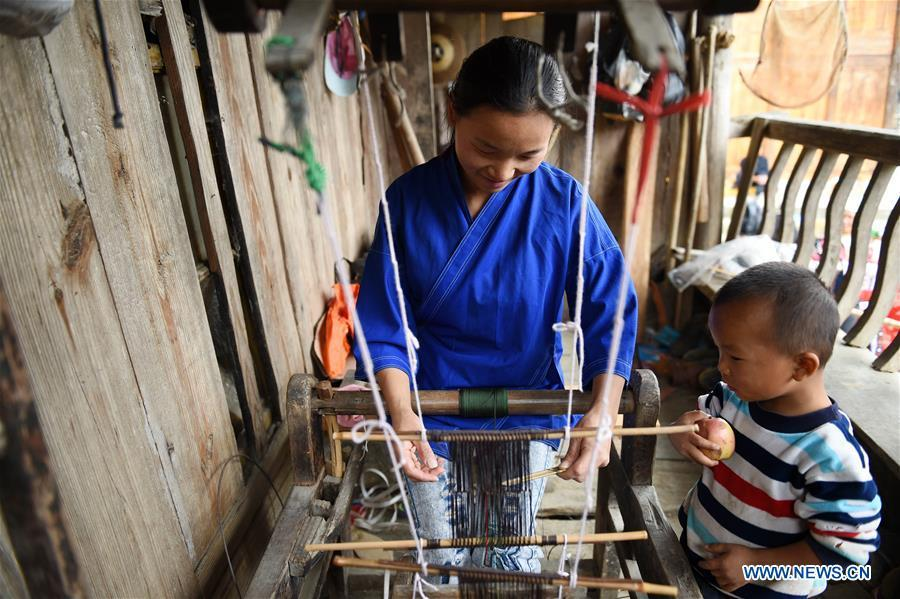 Yang Xinghe (L) weaves at Xinjiang Village in Taijiang County of Qiandongnan Miao and Dong Autonomous Prefecture, southwest China\'s Guizhou Province, on Nov. 4, 2018. Born with hearing loss, Yang Xinghe, 28, is a female of the Miao ethnic group, who are engaged in Miao embroidery at the village. She learned embroidery from her mother when she was only a child, and has been a locally well-known master now. (Xinhua/Liu Kaifu)