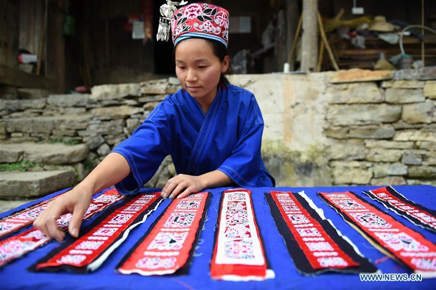 Yang Xinghe classifies embroidered decorations for Miao costumes at Xinjiang Village in Taijiang County of Qiandongnan Miao and Dong Autonomous Prefecture, southwest China\'s Guizhou Province, on Nov. 4, 2018. Born with hearing loss, Yang Xinghe, 28, is a female of the Miao ethnic group, who are engaged in Miao embroidery at the village. She learned embroidery from her mother when she was only a child, and has been a locally well-known master now. (Xinhua/Liu Kaifu)