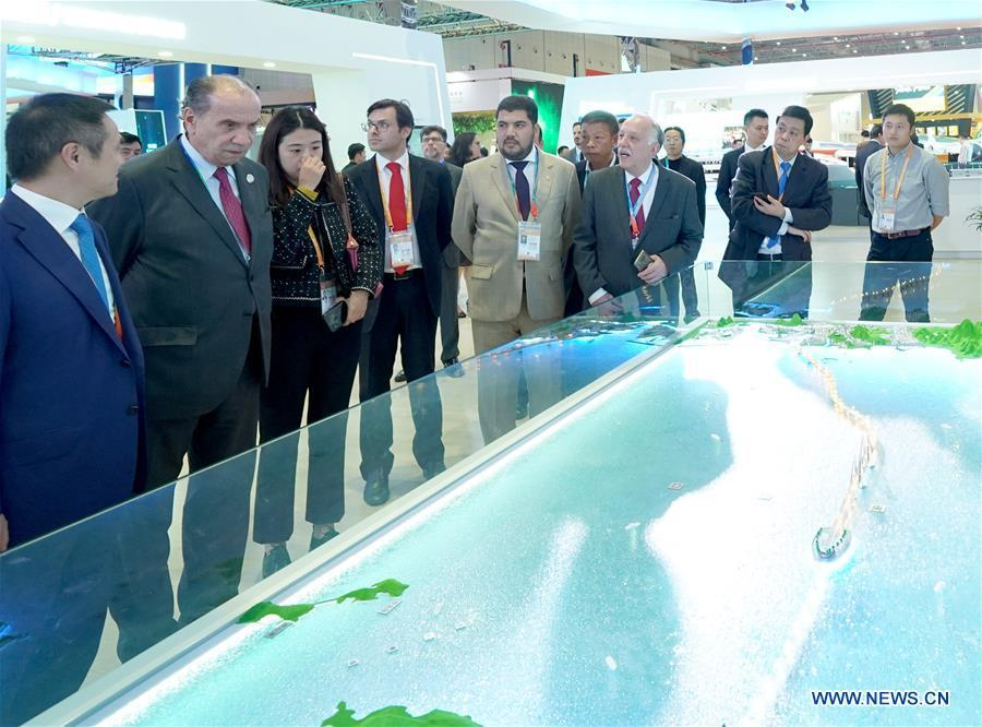 Brazilian government delegation view a model of the Hong Kong-Zhuhai-Macao bridge at the China Pavilion during the first China International Import Expo (CIIE) in Shanghai, east China, Nov. 5, 2018. A total of 82 countries and three international organizations showcased their achievements in economic and trade development as well as competitive products at 71 booths in the Country Pavilion for Trade and Investment at the CIIE.(Xinhua/Chen Jianli)