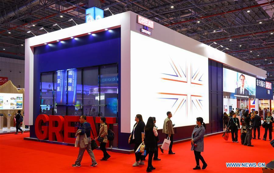 People walk past the United Kingdom pavilion during the first China International Import Expo (CIIE) in Shanghai, east China, Nov. 5, 2018. A total of 82 countries and three international organizations showcased their achievements in economic and trade development as well as competitive products at 71 booths in the Country Pavilion for Trade and Investment at the CIIE. (Xinhua/Liu Dawei)
