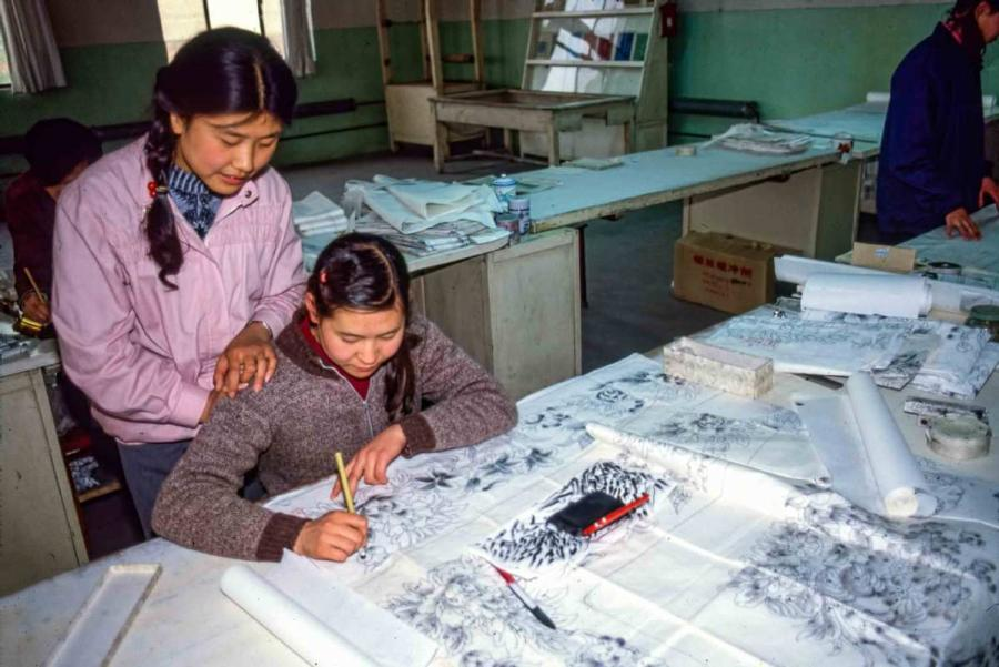 Sun Yuzhen watches as her colleague draws a sketch of a carpet. (Photo by Jamie Fouss/provided to chinadaily.com.cn)
