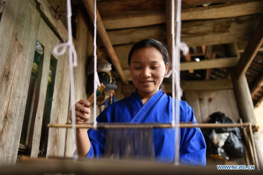 Yang Xinghe weaves at Xinjiang Village in Taijiang County of Qiandongnan Miao and Dong Autonomous Prefecture, southwest China\'s Guizhou Province, on Nov. 4, 2018. Born with hearing loss, Yang Xinghe, 28, is a female of the Miao ethnic group, who are engaged in Miao embroidery at the village. She learned embroidery from her mother when she was only a child, and has been a locally well-known master now. (Xinhua/Liu Kaifu)