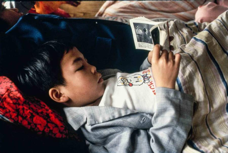 A boy reading a storybook on the boat from Guangzhou, South China\'s Guangdong province to Wuzhou, South China\'s Guangxi Zhuang autonomous region.  (Photo by Jamie Fouss/provided to chinadaily.com.cn)