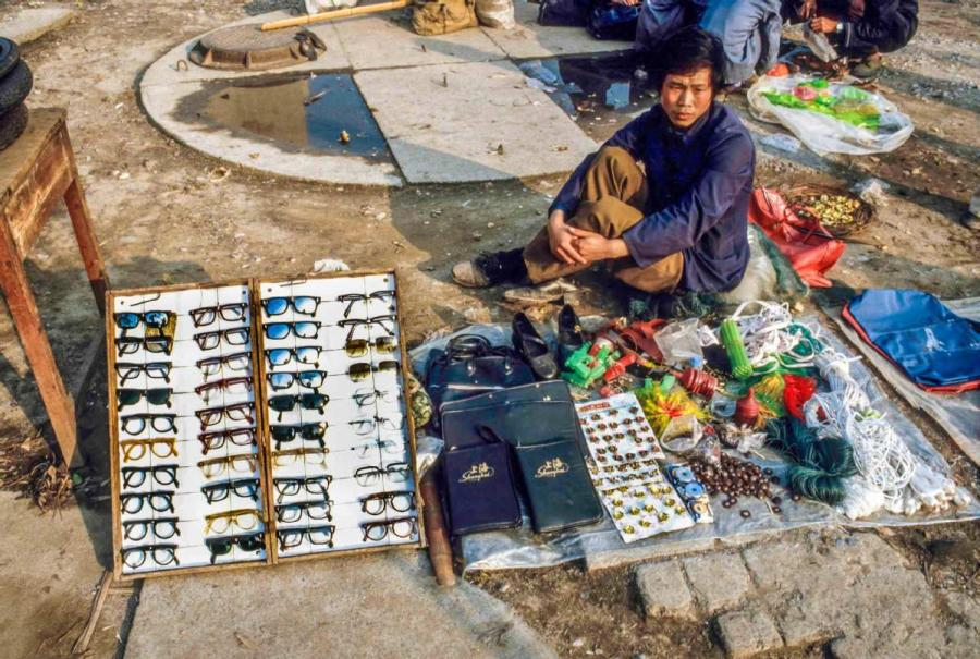 A man selling toys and sunglasses on the street in Guilin, South China\'s Guangxi Zhuang autonomous region.  (Photo by Jamie Fouss/provided to chinadaily.com.cn)