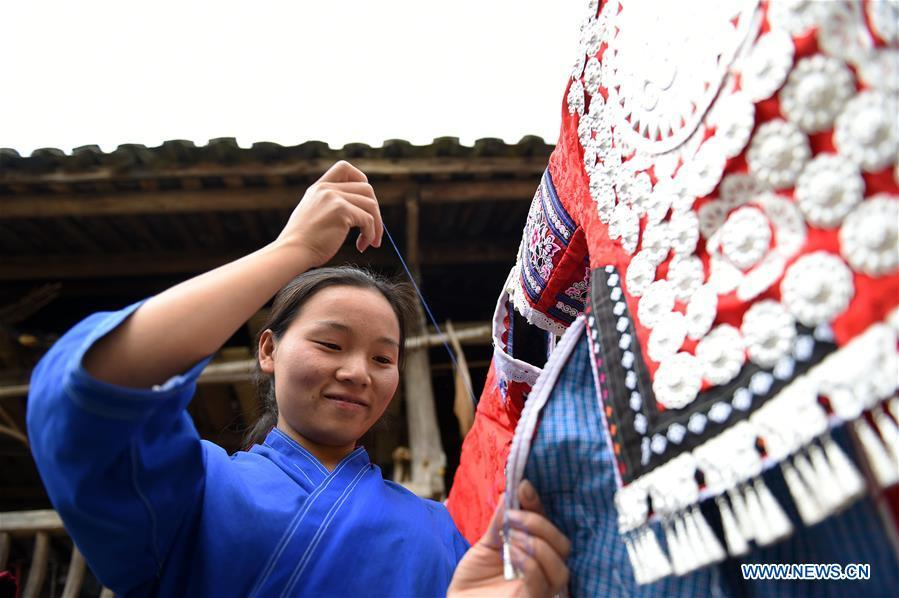Yang Xinghe embroiders Miao clothes at Xinjiang Village in Taijiang County of Qiandongnan Miao and Dong Autonomous Prefecture, southwest China\'s Guizhou Province, on Nov. 4, 2018. Born with hearing loss, Yang Xinghe, 28, is a female of the Miao ethnic group, who are engaged in Miao embroidery at the village. She learned embroidery from her mother when she was only a child, and has been a locally well-known master now. (Xinhua/Liu Kaifu)