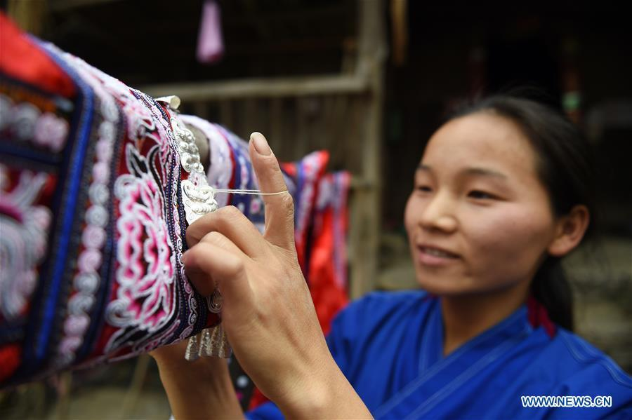 Yang Xinghe embroiders Miao costumes at Xinjiang Village in Taijiang County of Qiandongnan Miao and Dong Autonomous Prefecture, southwest China\'s Guizhou Province, on Nov. 4, 2018. Born with hearing loss, Yang Xinghe, 28, is a female of the Miao ethnic group, who are engaged in Miao embroidery at the village. She learned embroidery from her mother when she was only a child, and has been a locally well-known master now. (Xinhua/Liu Kaifu)