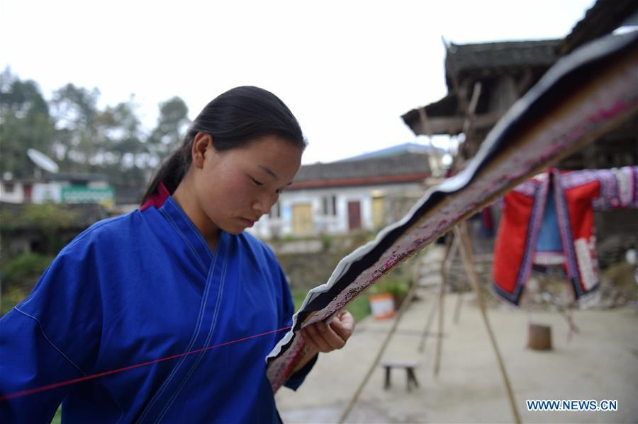 Yang Xinghe shows embroidery skills at Xinjiang Village in Taijiang County of Qiandongnan Miao and Dong Autonomous Prefecture, southwest China\'s Guizhou Province, on Nov. 4, 2018. Born with hearing loss, Yang Xinghe, 28, is a female of the Miao ethnic group, who are engaged in Miao embroidery at the village. She learned embroidery from her mother when she was only a child, and has been a locally well-known master now. (Xinhua/Liu Kaifu)