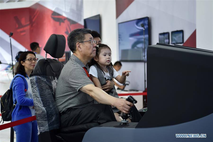 Citizens experience a flying simulator at the exhibition area of the upcoming China International Aviation and Aerospace Exhibition in Zhuhai, south China\'s Guangdong Province, Nov. 5, 2018. The exhibition is scheduled to be held on Nov. 6-11. (Xinhua/Liang Xu)