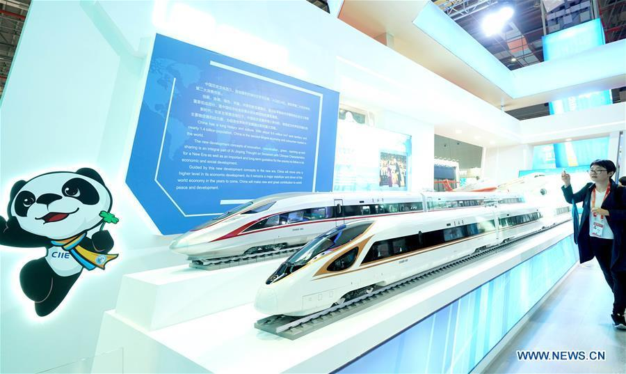 A journalist shoots models of China\'s Fuxing bullet train at the China Pavilion during the first China International Import Expo (CIIE) in Shanghai, east China, Nov. 5, 2018. A total of 82 countries and three international organizations showcased their achievements in economic and trade development as well as competitive products at 71 booths in the Country Pavilion for Trade and Investment at the CIIE. (Xinhua/Chen Jianli)