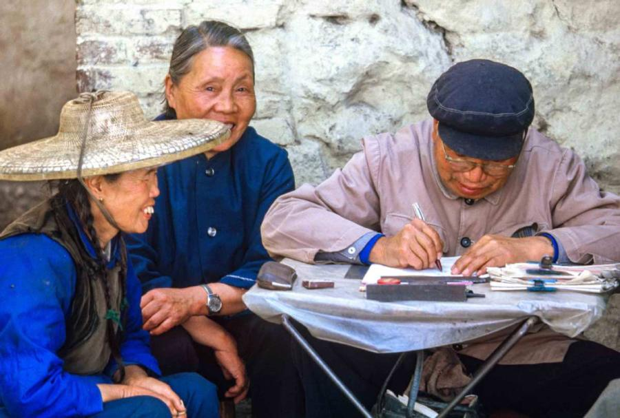 A man was helping the women to write a letter in Dali, Southwest China\'s Yunnan province. Dali was just opened to tourists two weeks before we arrived. We had to get special permission to go, so people there were very surprised to see us. It was a small town. In the hotel, there were crowds of people who wanted to talk to us to practice their English. (Photo by Jamie Fouss/provided to chinadaily.com.cn)