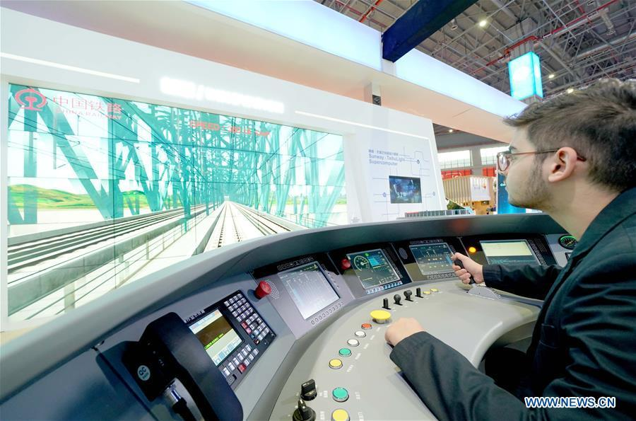 A member of Georgia\'s government delegation experiences a simulation of high-speed train driving at the China Pavilion during the first China International Import Expo (CIIE) in Shanghai, east China, Nov. 5, 2018. A total of 82 countries and three international organizations showcased their achievements in economic and trade development as well as competitive products at 71 booths in the Country Pavilion for Trade and Investment at the CIIE. (Xinhua/Chen Jianli)